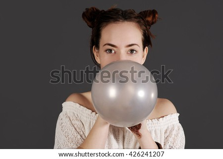 Funny young hipster woman is blowing a balloon. Studio shot with dark background. - stock photo