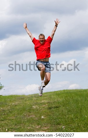 Funny young man high jumping in the field - stock photo