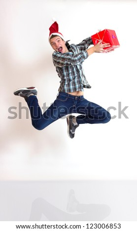 Funny young man in santa cap in hurry running or jumping with gifts - stock photo
