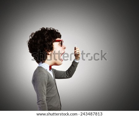 Funny young man with big head screaming emotional in mobile phone - stock photo