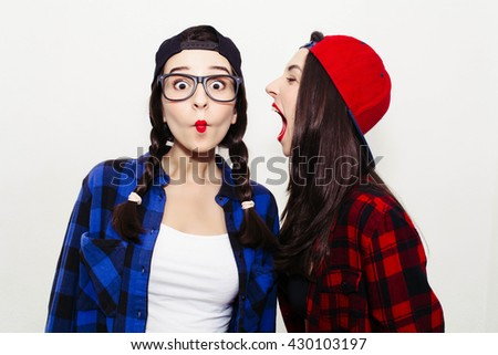 Funny young woman crazy shouting scream to another one. Colorful comic funny emotional hipster summer style twins teenager girls screaming, make faces and have fun. Isolated on a grey background - stock photo