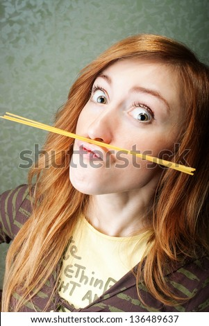 Funny young woman with spaghetti moustache - stock photo