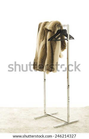 Fur Coat Draped Over Clothing Rack with Hangers in Studio with White Background - stock photo