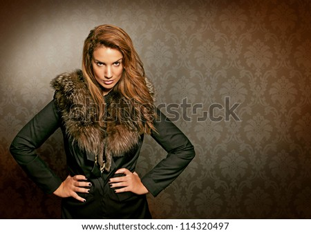 fur luxury lady with fur standing in front of a old wallpaper - stock photo