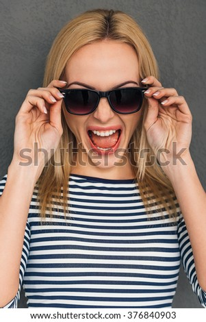 Furious and emotional. Beautiful young woman adjusting her sunglasses and keeping mouth open while standing against grey background - stock photo
