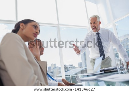 Furious boss yelling at colleagues during a meeting - stock photo