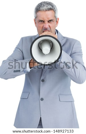 Furious businessman posing with loudspeaker on white background and looking at camera - stock photo