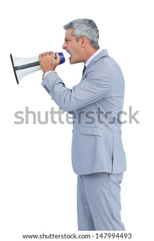 Furious businessman shouting in loudspeaker on white background - stock photo