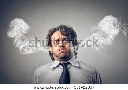 furious businessman with smoke coming out of his ears - stock photo
