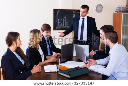 Furious head of company and frightened subordinate officials indoors. Focus on the left man - stock photo