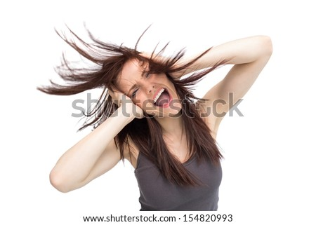Furious pretty brunette on white background tossing her hair - stock photo