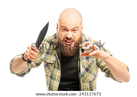 Furious young bearded caucasian man attacking with knife and shouting while standing against white background - stock photo