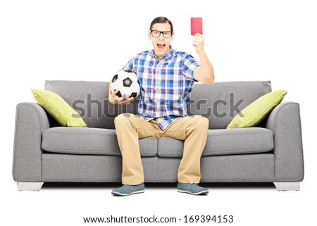 Furious young football fan sitting on sofa holding ball and giving a red card, isolated on white background - stock photo