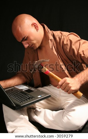 Furious young man destroying  laptop with a hammer - stock photo