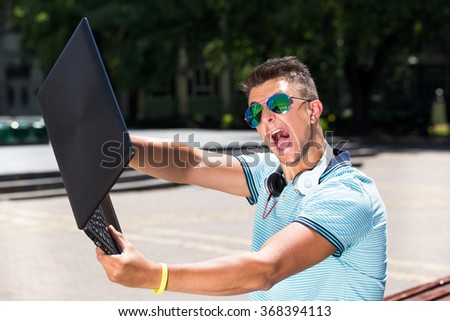 Furiously angry boy about to throw his notebook away - stock photo