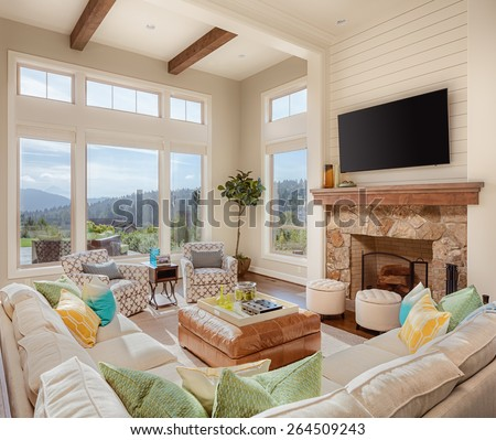 Furnished Living Room in Luxury Home on Sunny Day with Fireplace, TV, Large Bank of Windows, and Large Couch - stock photo