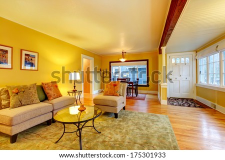 Furnished living room with entrance hall and dining area. Yellow walls great match with white plank ceiling and entrance door - stock photo
