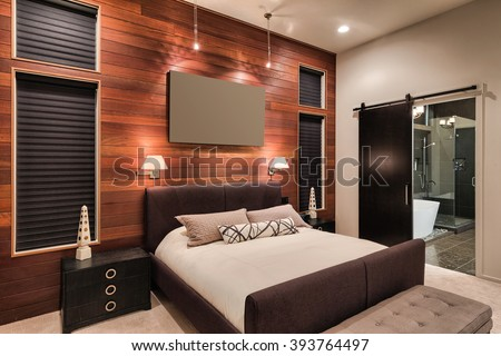 Furnished master bedroom interior in new home with view of bathroom including shower and bathtub - stock photo