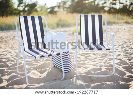 furniture and summer holidays concept - two beach lounges with beach bag and white hat on the beach - stock photo