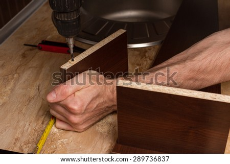 Furniture parts during drilling in the hands of builder of furniture. - stock photo