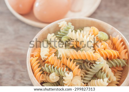 Fusili pasta in wooden plate with eggs, stock photo - stock photo