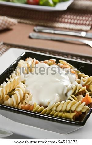 Fusilli colored with white sauce. Studio photogtraphy. - stock photo