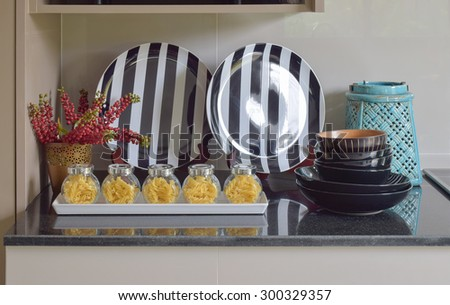 Fusilli jars and stripe plate setting on the counter - stock photo