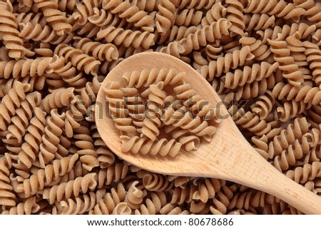 Fusilli pasta made with durham wheat in a wooden spoon and forming a background. - stock photo