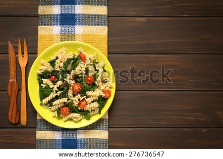 Fusilli pasta with chard leaves (lat. Beta vulgaris) and cherry tomatoes served on plate with wooden fork and knife on the side, photographed overhead on dark wood with natural light - stock photo