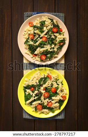 Fusilli pasta with chard leaves (lat. Beta vulgaris) and cherry tomatoes served on plates, photographed overhead on dark wood with natural light - stock photo