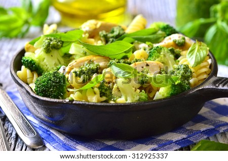 Fusilli with chicken,broccoli and basil pesto in a skillet pan. - stock photo