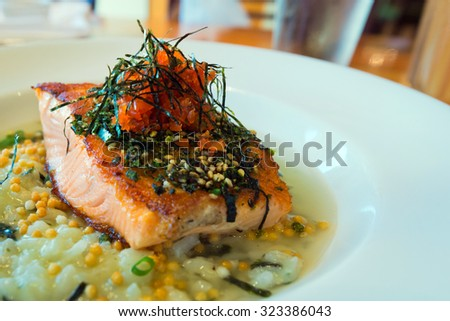 Fusion dish - cooked salmon fillet sprinkled with furikake, served on top of risotto - stock photo