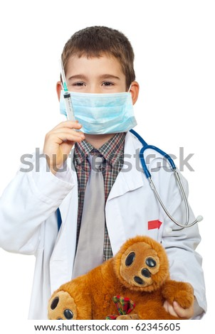 Future doctor boy with protective mask preparing to inject his teddy bear isolated on white background - stock photo