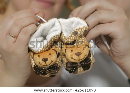 Future mom and dad holding little baby shoes. Happy young family awaiting baby, love and happiness, new life concept - stock photo
