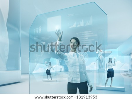 Future teamwork concept. Future technology touchscreen interface. Girl touching screen interface in hi-tech interior. Business lady pressing virtual button in futuristic office. - stock photo