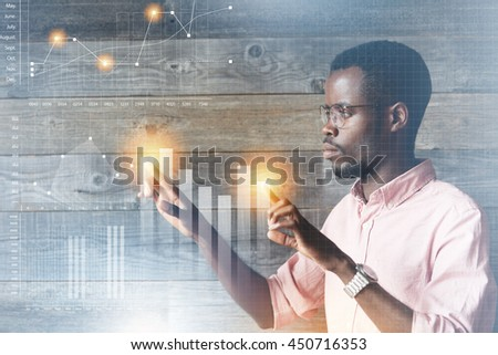 Future technology, touchscreen display interface. Handsome African American man working on modern computer, touching icons on futuristic screen, drawing diagrams, looking busy and concentrated - stock photo