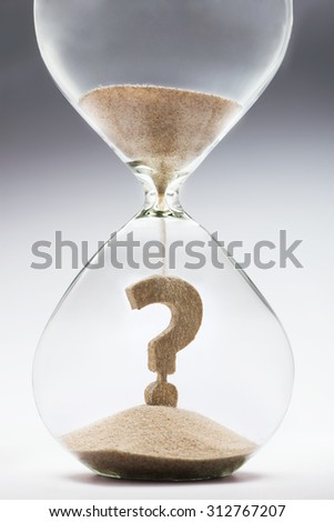 Future uncertainty. Question mark made out of falling sand inside hourglass - stock photo