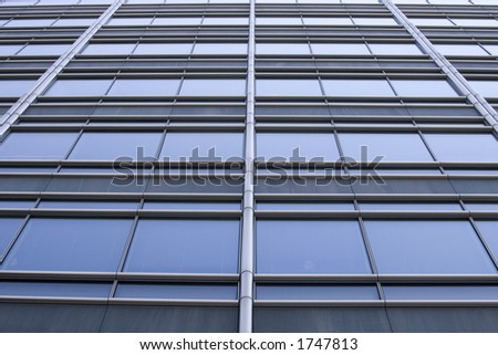 Futuristic abstract shot of the windows of a skyscraper. The lines from the windows are starting to converge to the center. - stock photo