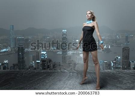 Futuristic fashion woman posing in small black dress at cityscape of night hongkong city - stock photo