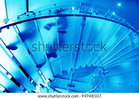 futuristic glass spiral staircase with modern building background - stock photo