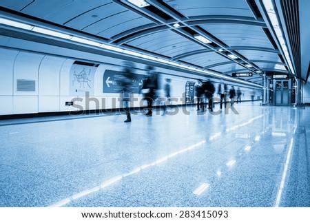 futuristic subway passage with passengers motion blur in guangzhou - stock photo