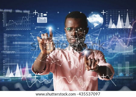 Futuristic technology. Double exposure. Portrait of African employee in glasses, looking at the camera with serious concentrated expression, touching screen interface against high-tech interior - stock photo