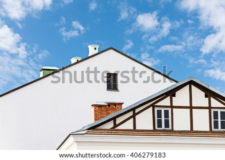gables of residential houses with windows and chimneys - stock photo