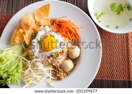 Gai pad bai gaprow style Thai dish with fried egg and rice noodles. - stock photo