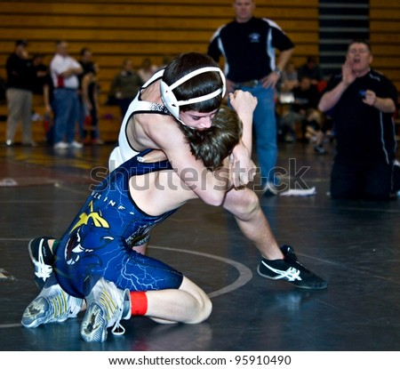 GAINESVILLE, GA, USA - FEB 11: Andy Leggett, winner, is held by an unidentified boy in the 11-14 division of a wrestling tournament, February, 11, 2012, at North Hall High School in Gainesville, GA. - stock photo