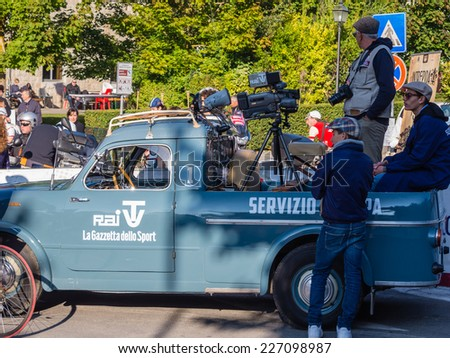 GAIOLE IN CHIANTI, ITALY - 5 OCT. 2014: Vintage press automobile at the start of L'Eroica, a cycling event for owners of vintage bicycles who ride a tour through Tuscany, mainly on white gravel roads - stock photo