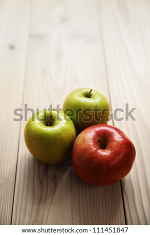 gala and two granny smith apples on wooden table - stock photo