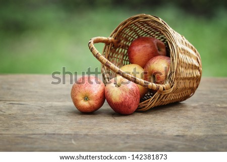 gala apples in a wicker basket, on wooden table - stock photo