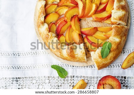 Galette with peaches on a white background. the toning. selective focus - stock photo