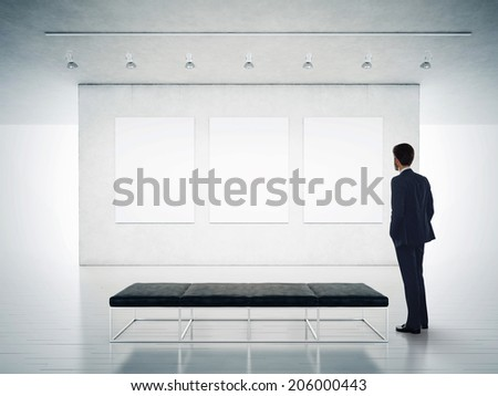 Gallery room and man looking at empty frames - stock photo